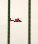A Coast Guard helicopter, seen between the suspension cables of the Mackinac Bridge, searches the waters of the Straits of Mackinac for a woman who reportedly either fell or jumped from the bridge.