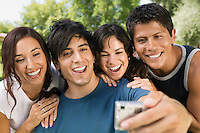 Young man using digital camera photographing self with three friends.