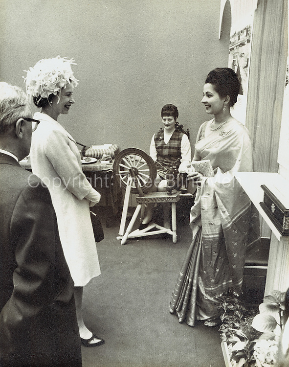Iranganie Gunatillake & 'Her Majesty' Mrs Iranganie Gunatillake, receptionist at the Ceylon Tea Centre in London, flew to Glasgow last month to meet the Queen. 1967. The occasion was the visit by Her Majesty and the Duke of Edinburgh to the new administrative building of the Scottish Co-operative Wholesale Society. Mrs Gunatillake showed the Queen a photographic display on the Ceylon Tea industry and a panel claiming that the SCWS supplies one third of all the tea consumed in Scotland. A reference was also made to the happy coincidence that the centenary of the SCWS corresponds closely to that of the Ceylon Tea Industry. Photo: courtesy Scottish Daily Record.