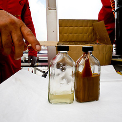 A worker points to sample bottles with water and oil separated from running oil through the Ocean Therapy Solutions oil separating centrifuge device during a demonstration on a vessel at Hornbeck Offshore in Port Fourchon, Louisiana, U.S., on Tuesday, June 15, 2010. (Mandatory Credit: Derick E. Hingle)