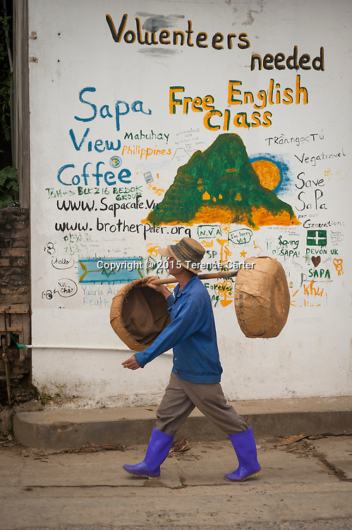 A market worker walks past a sign in Sapa, Vietnam.