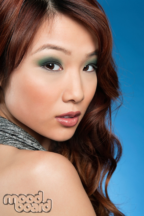 Portrait of beautiful young woman looking back over colored background