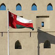 Oman, Bahla. March/06/2008...The Omani flag flying high at Bahla Fort.