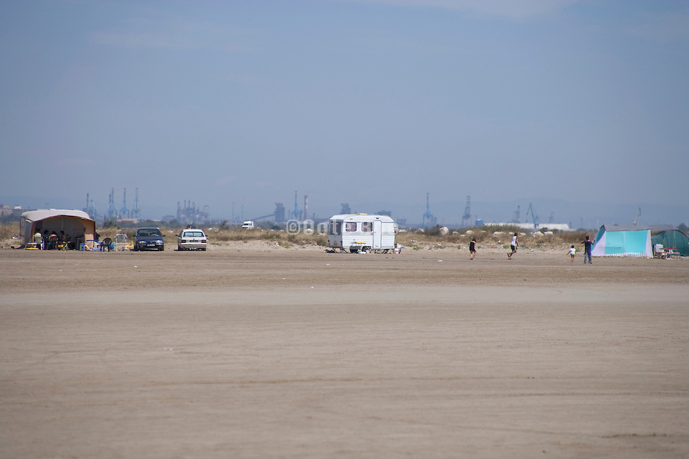 campers with oil refineries in the background