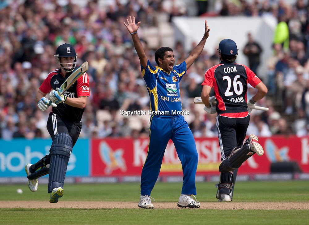 Bowler Dhammika Prasad appeals in vain for the lbw of Craig Kieswetter (left, with Alastair Cook) during the fifth and final one day international between England and Sri Lanka at Old Trafford, Manchester. Photo: Graham Morris (Tel: +44(0)20 8969 4192 Email: sales@cricketpix.com) 06/07/11