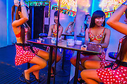 "12 JANUARY 2013 - BANGKOK, THAILAND:  Ladyboy entertainers check themselves in the mirror in front of the Cockatoo bar in the Soi Cowboy red light district in Bangkok. In Thai, the ladyboys are called kathoey. Many work in the entertainment and night life sectors of the Thai economy. Prostitution in Thailand is illegal, although in practice it is tolerated and partly regulated. Prostitution is practiced openly throughout the country. The number of prostitutes is difficult to determine, estimates vary widely. Since the Vietnam War, Thailand has gained international notoriety among travelers from many countries as a sex tourism destination. One estimate published in 2003 placed the trade at US$ 4.3 billion per year or about three percent of the Thai economy. It has been suggested that at least 10% of tourist dollars may be spent on the sex trade. According to a 2001 report by the World Health Organisation: ""There are between 150,000 and 200,000 sex workers (in Thailand).""    PHOTO BY JACK KURTZ"