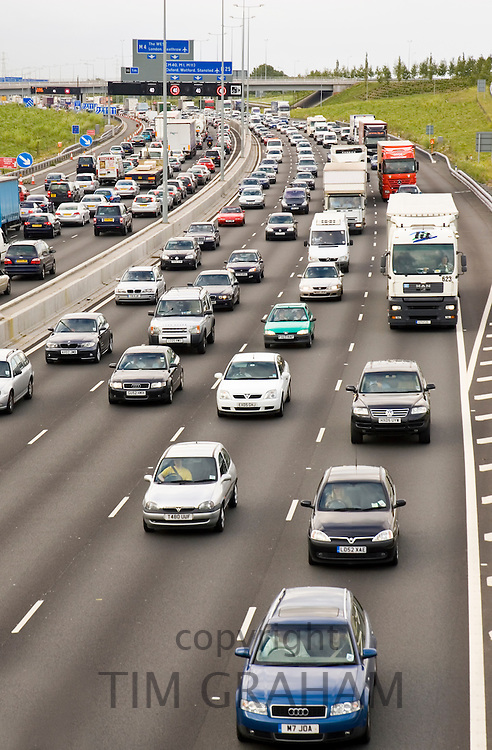 Four-lane traffic cars and trucks motoring in congestion on M25 motorway, London, United Kingdom