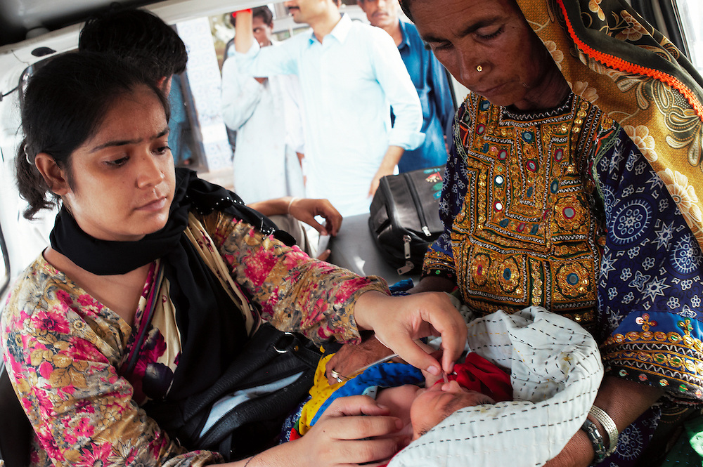 A one hour old baby with birth complications including mucus in the lungs is held by her grandmother and is treated with oxygen in an ambulance in the Bautoro District Hospital, Thatta, Sindh, Pakistan on July 1, 2011.