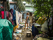 16 NOVEMBER 2015 - BANGKOK, THAILAND:  A woman hangs her laundry in the Wat Kalayanamit neighborhood. She's being evicted from her home and is one of the last people living in the neighborhood. Fifty-four homes around Wat Kalayanamit, a historic Buddhist temple on the Chao Phraya River in the Thonburi section of Bangkok, are being razed and the residents evicted to make way for new development at the temple. The abbot of the temple said he was evicting the residents, who have lived on the temple grounds for generations, because their homes are unsafe and because he wants to improve the temple grounds. The evictions are a part of a Bangkok trend, especially along the Chao Phraya River and BTS light rail lines. Low income people are being evicted from their long time homes to make way for urban renewal.          PHOTO BY JACK KURTZ
