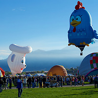 The low slung clouds of the Sandias open up into an azure blue sky for some early morning liftoff action at Balloon Fiesta