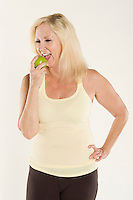 Beautiful mature woman eating a fresh green apple