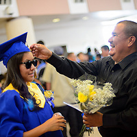 053113  Adron Gardner/Independent<br /> <br /> Chelsea Curley, left, gets a helping hand from Elliott Curley before graduation at Zuni High School in Zuni Friday.  The sunglasses were part of the &quot;Hollywood&quot; theme for seniors.