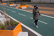 A woman concentrating on using her phone, walks on a new cycling path, a regenerated landscape created outside Croydon College and Fairfield Hall, on 20th January 2020, in Croydon, London, England.
