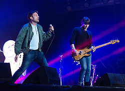© Licensed to London News Pictures. 13/06/2015. Isle of Wight, UK.   Blur performing live at Isle of Wight Festival 2015, Day 3 Saturday,headlining the main stage.  In this picture - Alex James (right), Damon Albarn (left).   Headline acts include The Prodigy, Blur and Fleetwood Mac.   Photo credit : Richard Isaac/LNP
