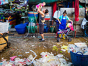 "04 DECEMBER 2018 - BANGKOK, THAILAND:  A man plays with his baby in front of a pile of plastic waste in Khlong Toei market. The issue of plastic waste became a public one in early June when a whale in Thai waters died after ingesting 18 pounds of plastic. In a recent report, Ocean Conservancy claimed that Thailand, China, Indonesia, the Philippines, and Vietnam were responsible for as much as 60 percent of the plastic waste in the world's oceans. Khlong Toey (also called Khlong Toei) Market is one of the largest ""wet markets"" in Thailand. December 4 was supposed to be a plastic free day in Bangkok but many market venders continued to use plastic.     PHOTO BY JACK KURTZ"