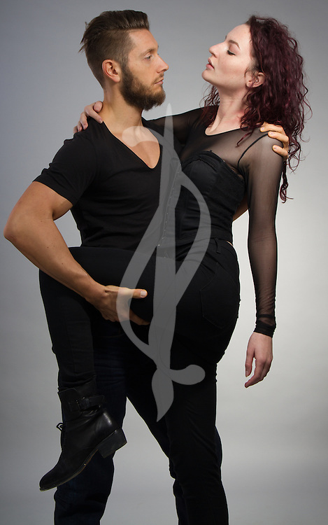 Couple posing in contemporary outfits.