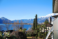 Ticino, Southern Switzerland. Lago Maggiore. Beautiful view across the lake to include mountains, pretty houses, and the deep blue lake and sky.