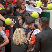 PARIS, FRANCE May 25. Novak Djokovic of Serbia helps a young fan caught in the crush for autographs after training on Court Suzanne Lenglen in preparation for the 2019 French Open Tennis Tournament at Roland Garros on May 25th 2019 in Paris, France. (Photo by Tim Clayton/Corbis via Getty Images)