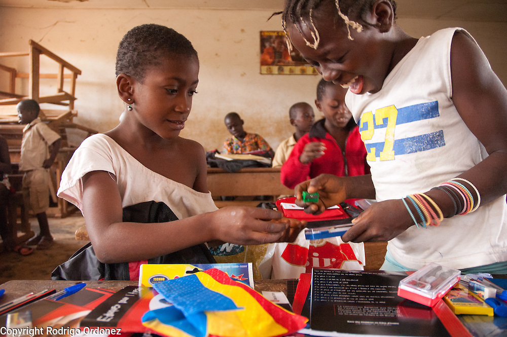 Dor&eacute;e (left), 9, and Carole, 11, smile while examining the contents of the backpacks with school materials they just received. <br /> Save the Children distributed education kits to students at Groupe Scolaire Quartier Lyc&eacute;e in Man, western C&ocirc;te d'Ivoire. Children received a backpack with school supplies such as pens, pencils, sharpeners, notebooks, rulers, a pair of compasses and a portable chalkboard.