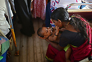 Mother calms a baby inside a public bus, Sri Lanka