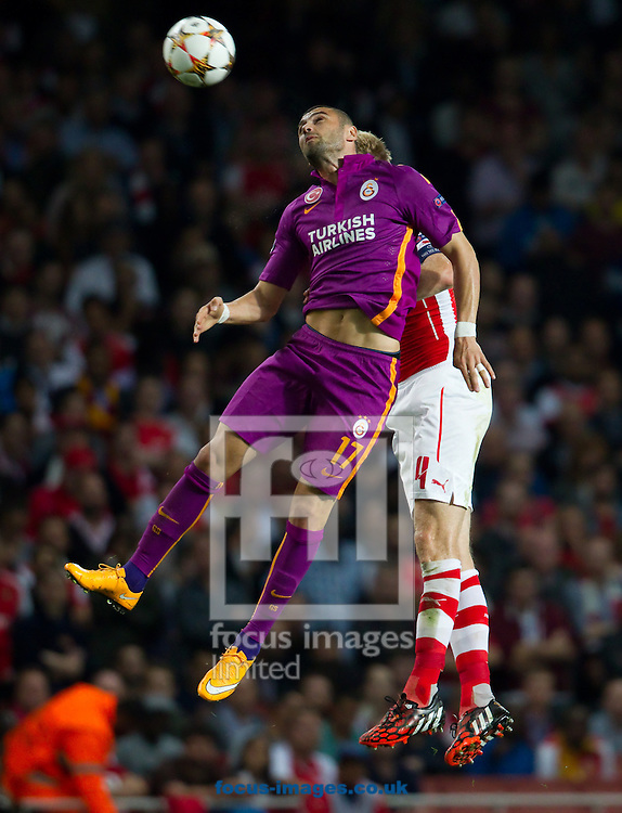 Per Mertesacker of Arsenal is beaten in the air by Burak Yilmaz of Galatasaray during the UEFA Champions League match at the Emirates Stadium, London<br /> Picture by John Rainford/Focus Images Ltd +44 7506 538356<br /> 01/10/2014