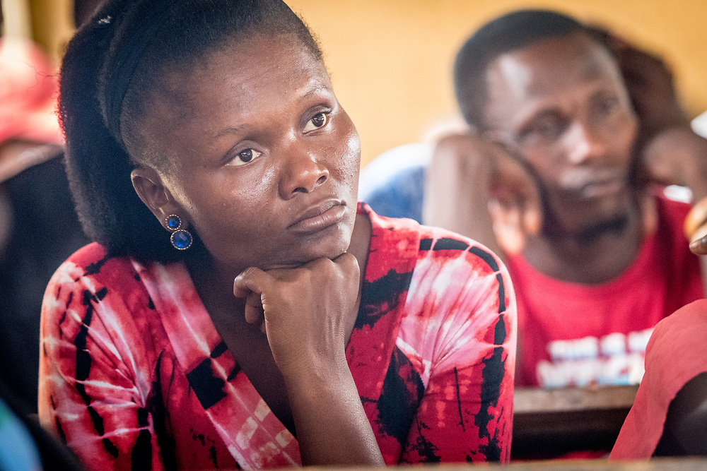 A woman focuses on the speaker of a lesson in Ganta, Liberia