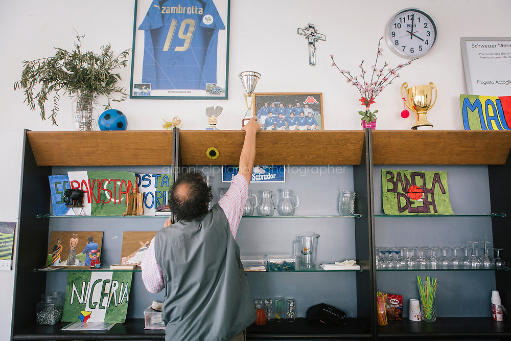COMO, ITALY - 21 JUNE 2017: Giusto Della Valle, a local priest who since 2011 has run a center on the outskirts of town where more than 50 migrants sleep at night, picks the soccer trophy the refugees he hosts won in a tournament for National Refugee Day this month in Como, Italy, on June 21st 2017.<br /> <br /> Residents of Como are worried that funds redirected to migrants deprived the town&rsquo;s handicapped of services and complained that any protest prompted accusations of racism.<br /> <br /> Throughout Italy, run-off mayoral elections on Sunday will be considered bellwethers for upcoming national elections and immigration has again emerged as a burning issue.<br /> <br /> Italy has registered more than 70,000 migrants this year, 27 percent more than it did by this time in 2016, when a record 181,000 migrants arrived. Waves of migrants continue to make the perilous, and often fatal, crossing to southern Italy from Africa, South Asia and the Middle East, seeing Italy as the gateway to Europe.<br /> <br /> While migrants spoke of their appreciation of Italy&rsquo;s humanitarian efforts to save them from the Mediterranean Sea, they also expressed exhaustion with the country&rsquo;s intricate web of permits and papers and European rules that required them to stay in the country that first documented them.