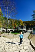 Child eating ice-cream, walking toward camera, away from boat on lake. Plitvice National Park, Croatia