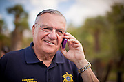 12 JUNE 2010 - PHOENIX, AZ: Maricopa County Sheriff Joe Arpaio talks to supporters via cell phone at a Tea Party rally in support of Arizona bill SB 1070 in Phoenix, AZ, Saturday. About 500 people, many from California and Florida, came to Bolin Memorial Park in Phoenix Saturday. The pro SB 1070 rally was sponsored by Tea Party.   PHOTO BY JACK KURTZ