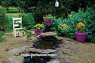 63821-15109 Backyard landscape with water feature, purple containers, and yellow chair Marion Co. IL