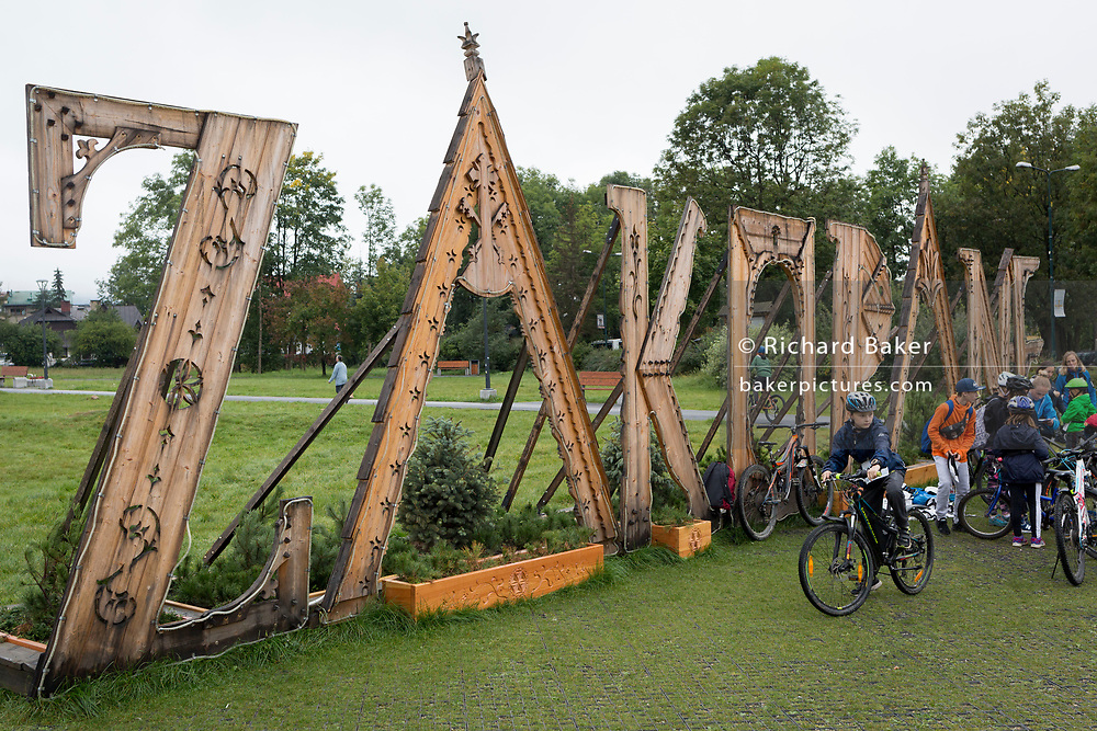 Young local Polish schoolchildren take part in a cycling challenge held in an open green space and in front of large wooden lettering for their southern Polish town, on 17th September 2019, in Zakopane, Malopolska, Poland.