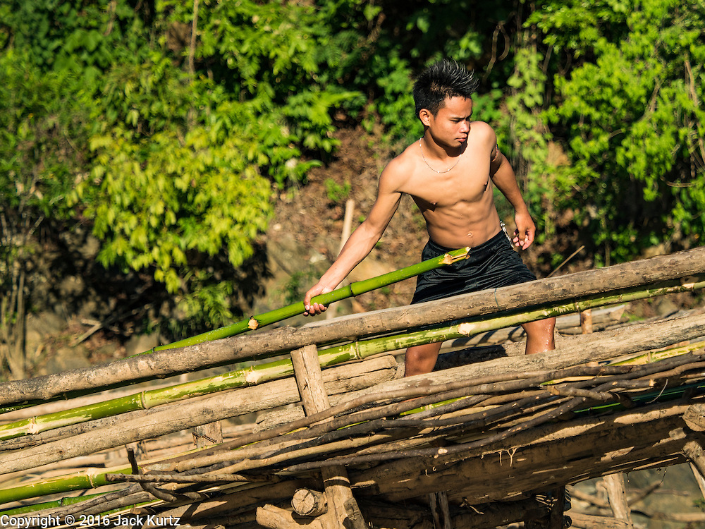 18 JUNE 2016 - DON KHONE, CHAMPASAK, LAOS: Fishermen work on their fish traps at Khon Pa Soi Waterfalls, on the east side of Don Khon. It's the smaller of the two waterfalls in Don Khon. Fishermen have constructed an elaborate system of rope bridges over the falls they use to get to the fish traps they set. Fishermen in the area are contending with lower yields and smaller fish, threatening their way of life. The Mekong River is one of the most biodiverse and productive rivers on Earth. It is a global hotspot for freshwater fishes: over 1,000 species have been recorded there, second only to the Amazon. The Mekong River is also the most productive inland fishery in the world. The total harvest of fish from the Mekong is approximately 2.5 million metric tons per year. By some estimates the harvest in the Tonle Sap (in Cambodia) had doubled from 1940 to 1995, but the number of people fishing the in the lake has quadrupled, so the harvest per person is cut in half. There is evidence of over fishing in the Mekong - populations of large fish have shrunk and fishermen are bringing in smaller and smaller fish.     PHOTO BY JACK KURTZ