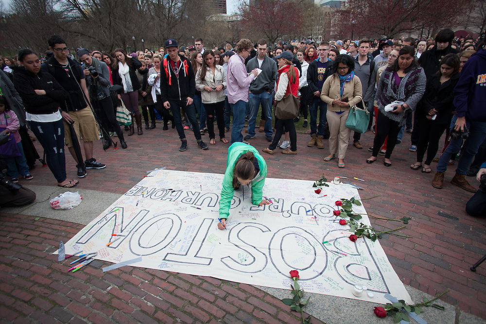 People write messages on a canvas banner during a vigil for the victim's of Monday's terrorist bombings near the finish line of the Boston Marathon, on Boston Common in Boston, MA on Tuesday, April 16, 2013.  (Matthew Cavanaugh for The Washington Post)