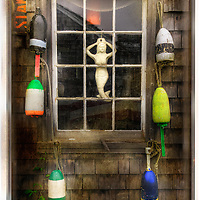 Mermaid hanging in old sailor tack room window with colorful bouys.