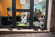 Un bambino italiano guarda incuriosito gli uomini che pregano dentro un negozio di immigrati del Bangladesh, prima del Iftar, la cena che rompe il digiuno nel mese del Ramadan. Roma 18 Agosto 2011<br />