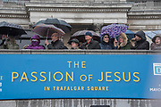 The crowd takes cover from the rain - The Wintershall Players open-air re-enactment of 'The Passion of Jesus' on Good Friday in the rain in Trafalgar Square. It featured a cast of over 100 volunteers from in and around London.