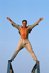 Young man with an open shirt enjoying himself balancing on wooden railings