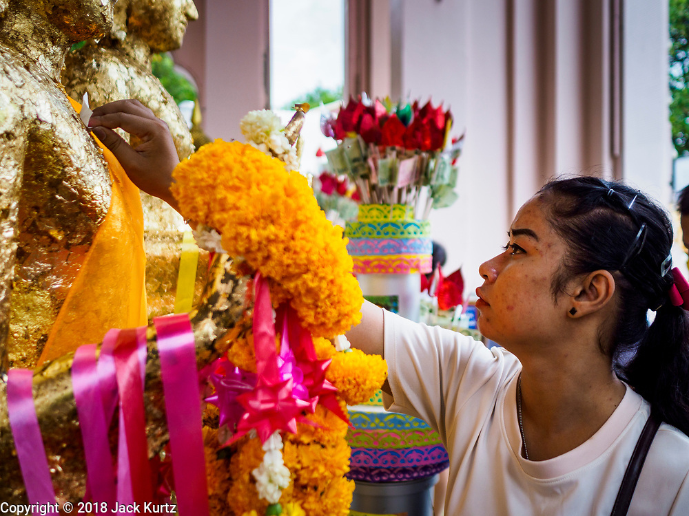 10 JULY 2018 - NAKHON PATHOM, THAILAND:  A woman makes merit at Phra Pathom Chedi in Nakhon Pathom. Nakhon Pathom is about 35 miles west of Bangkok. It is one of the oldest cities in Thailand, archeological evidence suggests there was a settlement on the site of present Nakhon Pathom in the 6th century CE, centuries before the Siamese empires existed. The city is widely considered the first Buddhist community in Thailand and the nearly 400 foot tall Phra Pathom Chedi is considered the first Buddhist temple in Thailand.    PHOTO BY JACK KURTZ