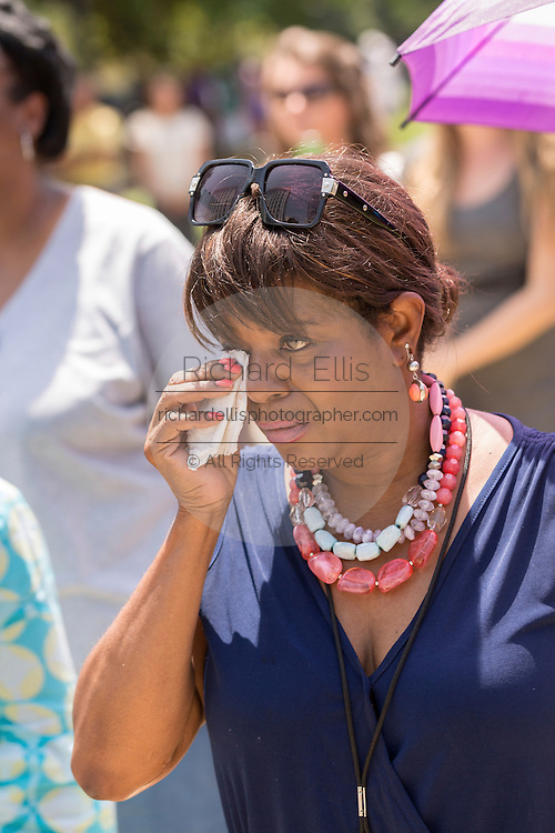 A mourner wipes away a tear as the horse-drawn caisson carrying the casket of slain State Senator Clementa Pinckney arrives at the State House June 24, 2015 in Columbia, South Carolina. Pinckney is one of the nine people killed in last weeks Charleston church massacre.