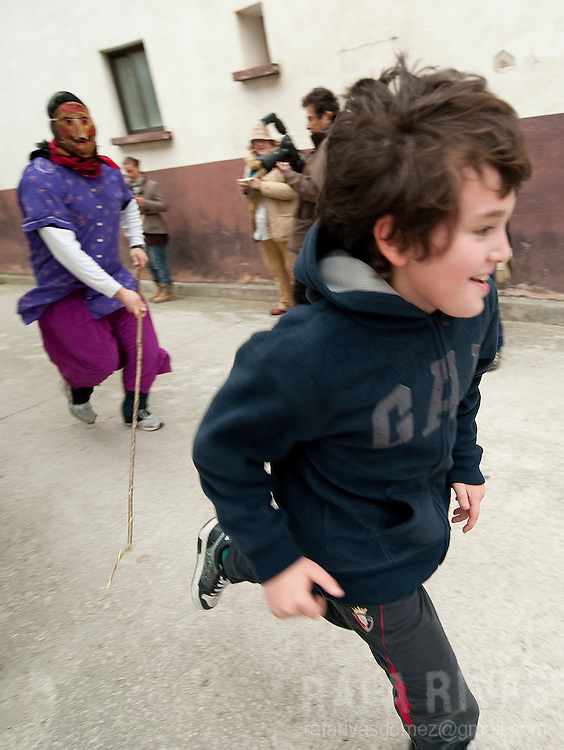 A momotxorro chases a boy during the ancient carnival of Unanu, North of Navarra province in Spain, on March 8, 2011. Momotxorros chase locals and slash them with sticks.  PHOTO/ RAFA RIVAS