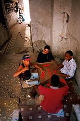 Youths play dominos in rundown apartment building in Havana, Cuba. (Photo © Jock Fistick)