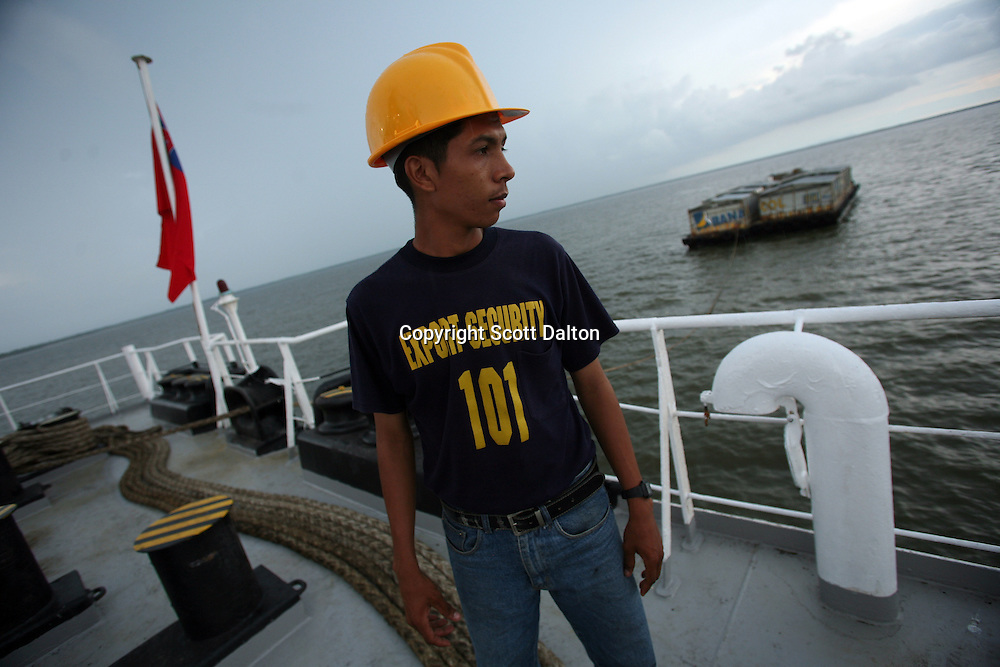 A security officer keeps watch from the deck of one ship carrying Colombian bananas, in the Gulf of Turbo, along Colombia?s northern coast, on July 10, 2007. Colombia?s banana region has long a stronghold for illegal armed groups who apparently funded their wars by taxing the banana industry. American banana executives of the Cincinnati-based fruit giant Chiquita have acknowledged making monthly protection payments for six years to illegal groups that killed thousands of people. (Photo/Scott Dalton)