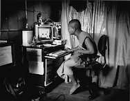 Monk Ven Dhammachoto Suy Vuth, head monk at Attiksmosan Pagoda, working on a computer in his chamber, Siem Reap, Cambodia.