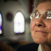 """Sister Andrea Verchuck, looks up at the stained glass inside the Immaculate Conception Chapel at the Saint Benedict Monastery, in Bristow, VA.  The Benedictine Sisters of Virginia dates back to 1868, Saint Benedict Monastery was built in 1901 and the Chapel in 1933.  Sister Andrea joined the Monastery in 1950 when she was only 15.  She says about her decision to become a nun at such an early age, """"I think the most rewarding thing was an assurance that this is what I was meant to do.  I have had more happiness and more satisfaction and more fulfillment in this than in anything I think I could do."""""""