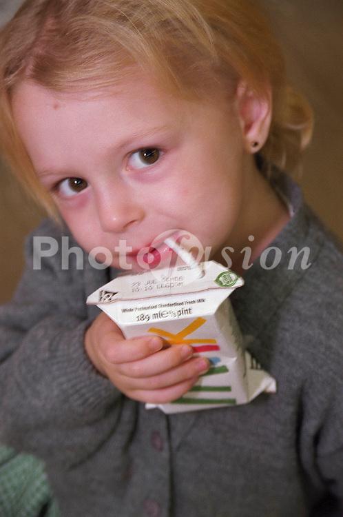 Nursery school girl drinking milk from carton through straw,