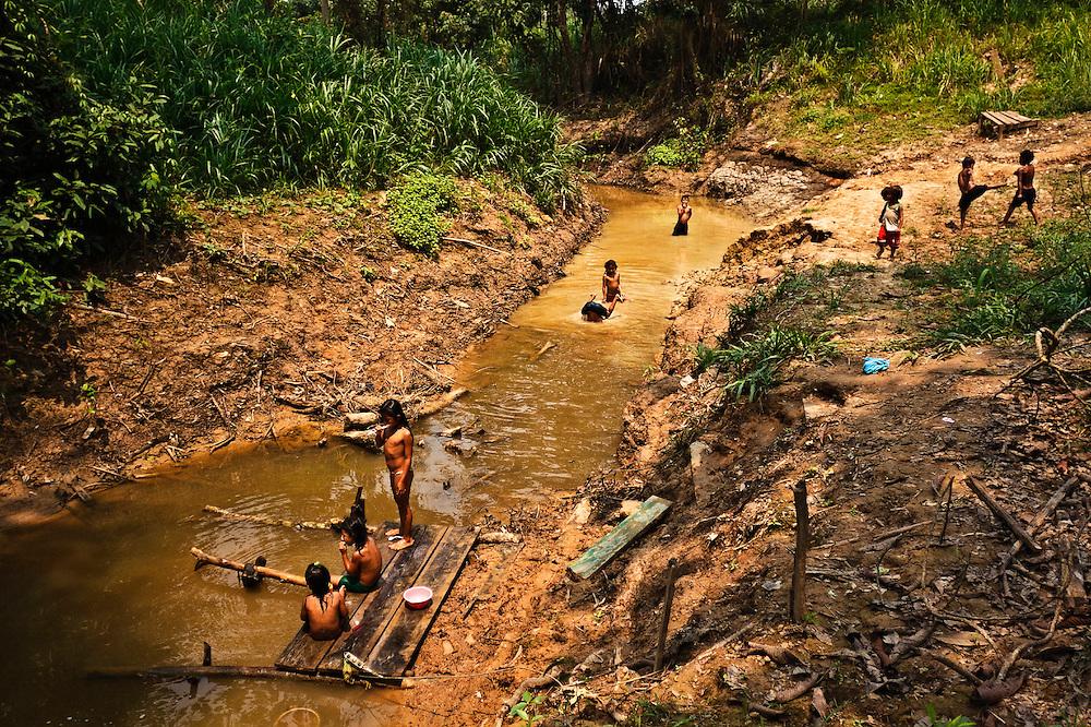 Colombia, Amazonas, Macedonia, 2010. Macedonia. <br /> Macedonia es un diminuto poblado ind&iacute;gena clavado en la selva amaz&oacute;nica colombiana. Como el agua tambi&eacute;n fluye la vida de los ni&ntilde;os que crecen a orillas del r&iacute;o m&aacute;s caudaloso y largo del mundo. Un misionero fund&oacute; este pueblo hace poco menos de cincuenta a&ntilde;os; hoy d&iacute;a todos sus habitantes viven la doctrina evangelista que deform&oacute; sus tradicionales pr&aacute;cticas culturales. <br /> Macedonia is a tiny indigenous town in the Colombian amazonian forest. As the water flows it also shapes the lives of the children growing up along the shore of the most mighty and longest river in the world.  A missionary founded this town around fifty years ago; today all inhabitants live the evangelist doctrine that replaced their traditional cultural practices.