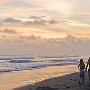 A couple walks on the beach while holding hands, in Dominical, Costa Rica. Dominical is know for its huge waves and chilled-out atmosphere. Photo by William Drumm.