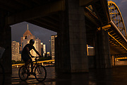 A man bikes under the Fort Duquesne bridge as storms move out of the area, Sunday, June 24, 2018, in North Shore. (Harrison Jones/Post-Gazette)