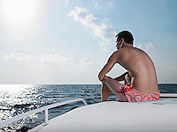 Young man sitting at edge of yacht looking at sea back view