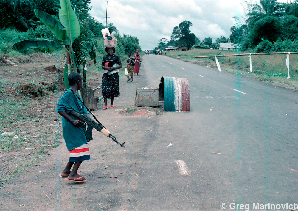 IPMG0910 Bo Waterfront, Liberia. A child soldier loyal to Sekouh Conneh Jr's LRD rebels mans a roadblock on the road between Monrovia and the border crossing with Sierra leone at Bo Waterfront, Sept 22, 2003. Liberia's decades long civil conflict has destabilised the entire region and turned a generation of youth into fighters.  Greg Marinovich/South Photographs